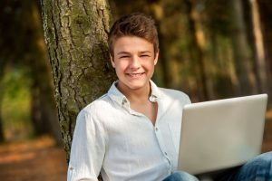 teen boy with laptop smiling